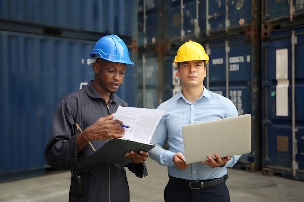 Gerente e trabalhador portuário em discussão sobre documento de armazém de remessa de contêiner de doca, eles usam capacete de uniforme de segurança, máscara facial e mantém comunicação por rádio.