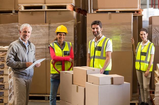 Gerente e trabalhadores estão sorrindo e posando