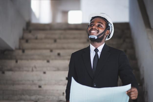 Gerente engenheiro de arquitetos africanos com tablet trabalhando juntos no interior do canteiro de obras