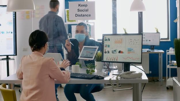 Gerente executiva com máscara facial mostrando estatísticas para seu colega usando um computador tablet digital. colegas de trabalho trabalhando em um novo escritório normal, mantendo distância social para prevenir a infecção com covi