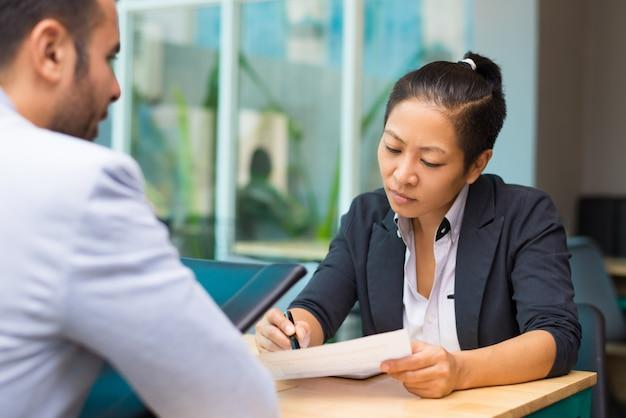 Gerente executivo asiático pensativo que se encontra com um candidato a emprego