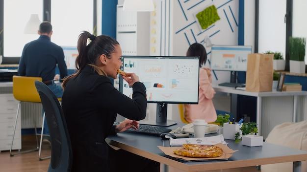 Gerente executivo comendo pizza saborosa enquanto digita estatísticas financeiras na mesa de trabalho
