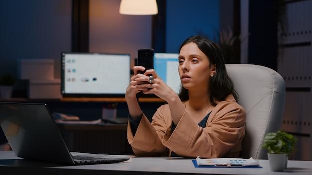 Gerente executivo sobrecarregado segurando ideias de marketing de mensagens de texto por telefone, analisando a estratégia de mídia social, sentado à mesa no escritório da empresa