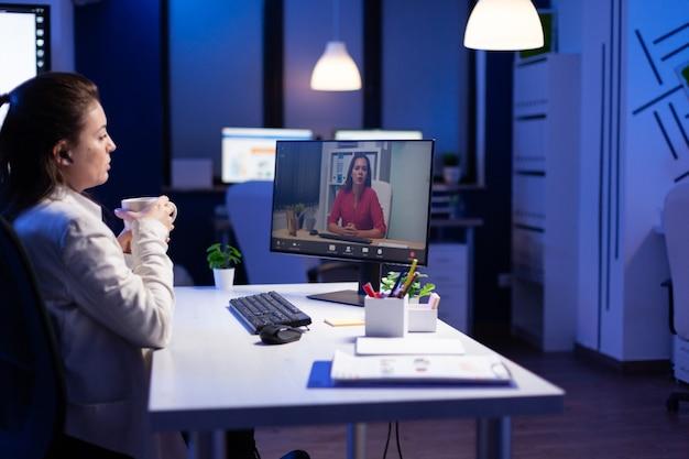 Gerente falando com colegas de chá durante a teleconferência online