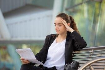 Gerente fêmea focalizado que revê o relatório de vendas