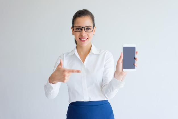 Gerente fêmea novo satisfeito positivo que aponta na tela do dispositivo.