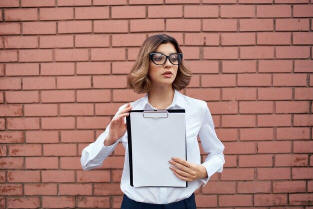 Gerente feminina ao ar livre com documentos na mão luz de fundo