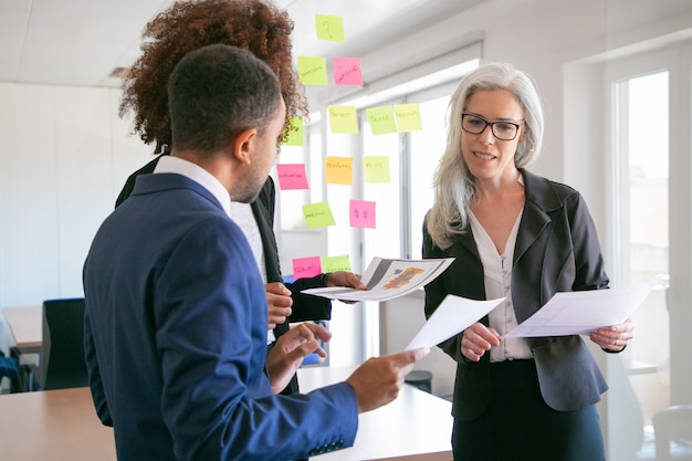 Gerente feminina de conteúdo explicando dados estatísticos aos colegas. parceiros de negócios profissionais, ouvindo a experiente empresária de cabelos grisalhos na sala de conferências. trabalho em equipe e conceito de gestão