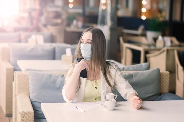 Gerente feminina em um terno e máscara médica trabalha remotamente no café de rua.