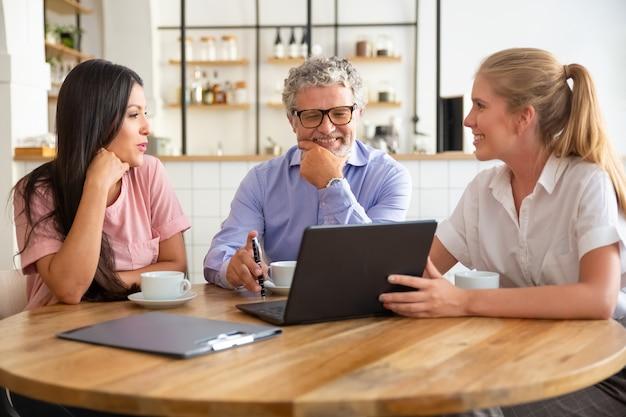 Gerente feminina feliz apresentando o projeto no laptop para uma jovem e um homem maduro, discutindo o conteúdo com clientes satisfeitos