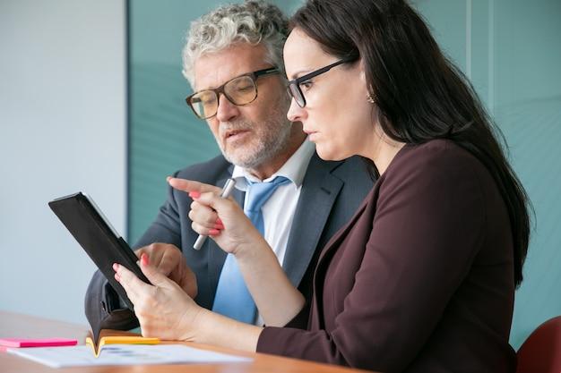 Gerente feminina mostrando relatório sobre tablet para chefe masculino