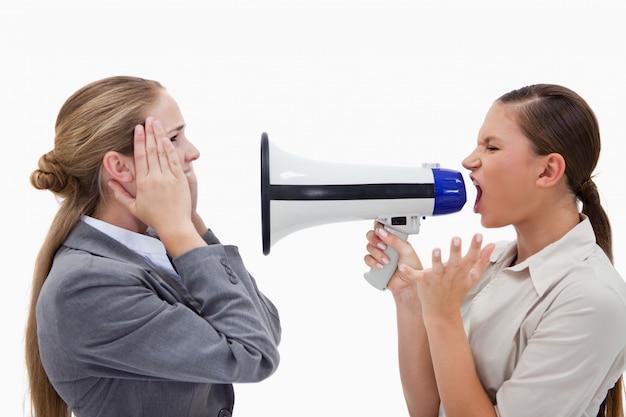 Gerente gritando com seu empregado através de um megafone
