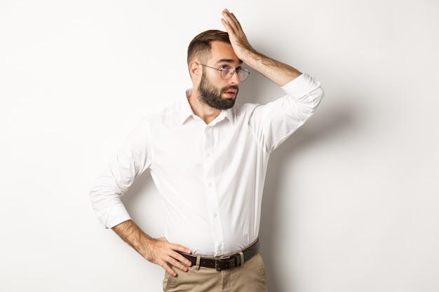 Gerente homem irritado revira os olhos e dá um tapa na testa, palma da mão de algo cansativo, de pé sobre um fundo branco.