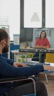 Gerente inválido conversando com um colega de trabalho durante a videoconferência