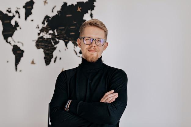 Gerente masculino bonito olhando e sorrindo enquanto está sentado no escritório moderno de luz. jovem fazendo planos de negócios