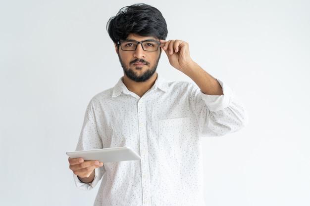 Gerente masculino concentrado sério com a tabuleta que ajusta vidros e que olha a câmera.