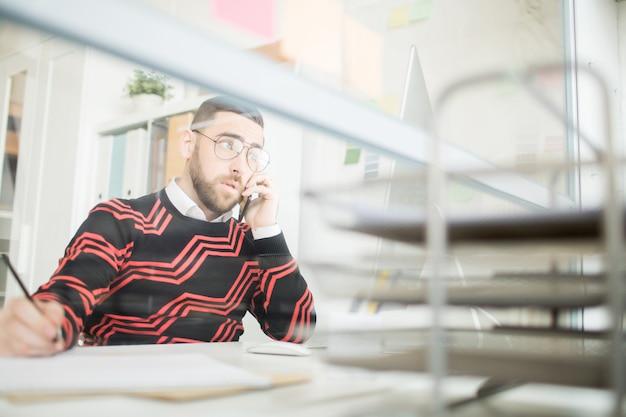 Gerente masculino confiante, falando pelo telefone móvel