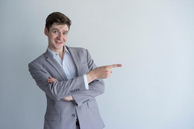 Gerente masculino empreendedor positivo que aponta de lado e que olha a câmera.