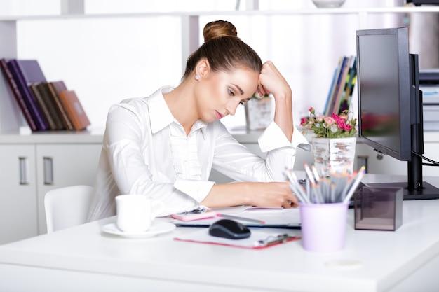 Gerente mulher cansada no escritório após um dia duro de trabalho