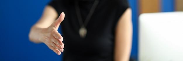Gerente mulher oferecendo a mão do cliente para apertar e assistência comercial durante a visita oficial em close-up do escritório