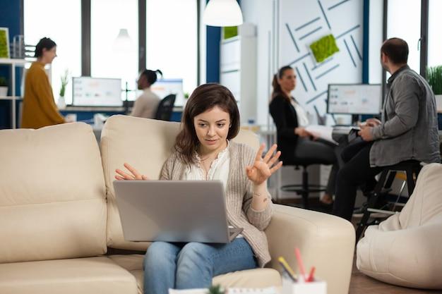 Gerente mulher sentada no sofá segurando laptop e falando na videochamada durante