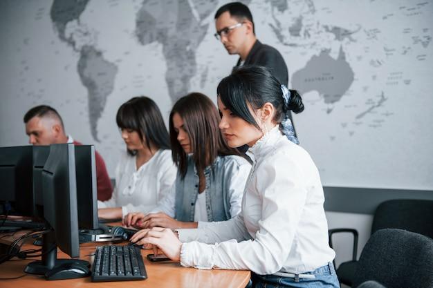 Gerente olhando para o trabalho do funcionário. grupo de pessoas em conferência de negócios em sala de aula moderna durante o dia
