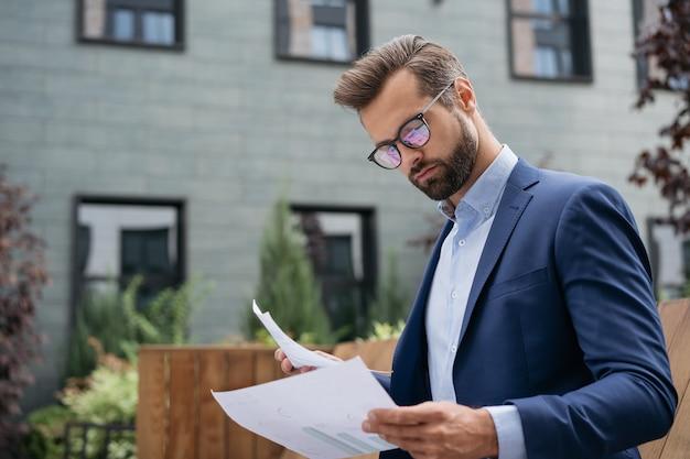 Gerente pensativo, planejando um projeto segurando um relatório financeiro. contrato de leitura do empresário