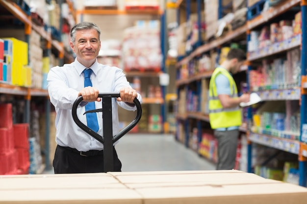 Gerente puxando o carrinho com caixas na frente de seu empregado