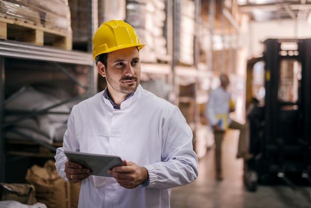 Gerente segurando o tablet e verificação de mercadorias no armazém.