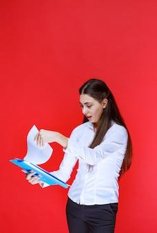 Gerente segurando uma pasta azul e checando os relatórios com surpresa.