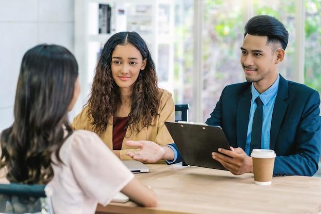 Gerente sênior asiático explicando ou respondendo sobre a descrição do trabalho e benefícios para a jovem mulher asiática