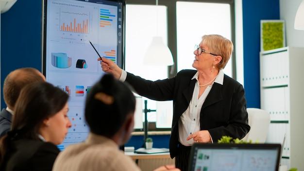 Gerente sênior executivo sério e diversas pessoas da equipe analisando o briefing da apresentação do projeto digital, compartilhando ideias em trabalho em equipe, discutindo o plano financeiro na sala de reuniões corporativas do escritório