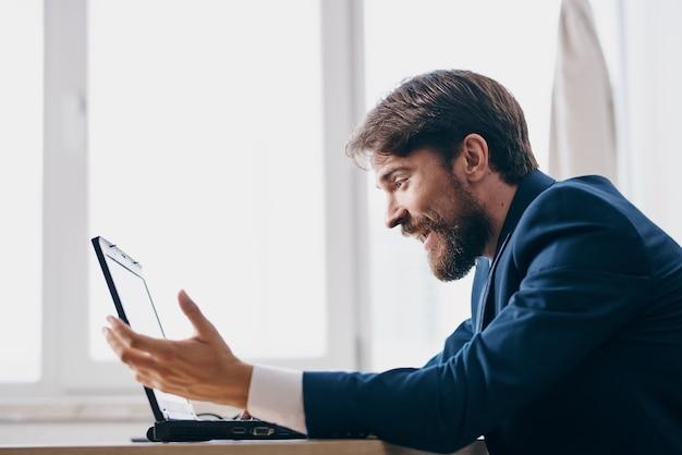 Gerente sentado em uma mesa em frente a tecnologias de rede financeira de laptop