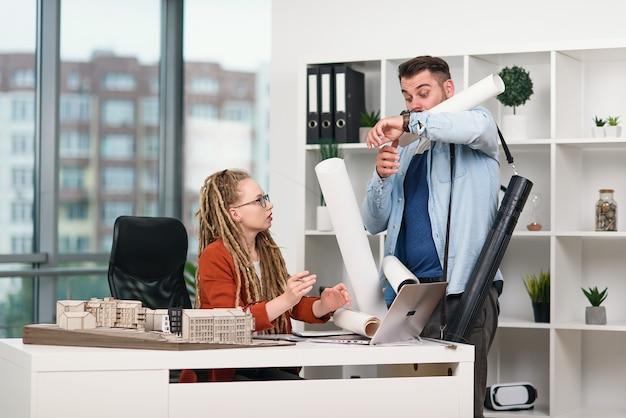 Gerente séria da agência de design fica chateada quando uma trabalhadora desajeitada expõe plantas em sua mesa
