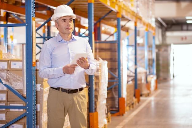 Gerente sério e inteligente segurando um tablet enquanto controla o processo de trabalho