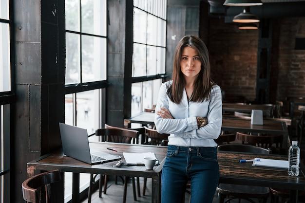 Gerente sério. mulher de negócios com roupas oficiais está dentro de casa no café durante o dia.