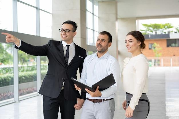 Gerente sorridente mostrando objeto imobiliário para investidores