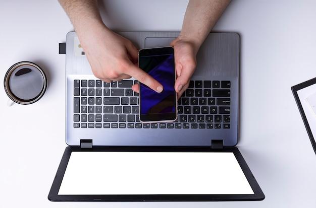 Gerente trabalha com laptop e smartphone