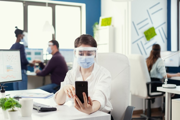 Gerente usando smartphone para conferência online usando máscara contra covid-19 como medida de segurança