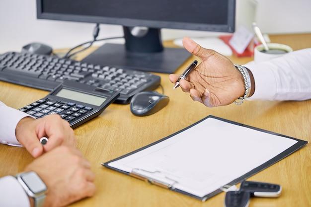 Gerente útil da concessionária dá as informações e instruções necessárias aos clientes