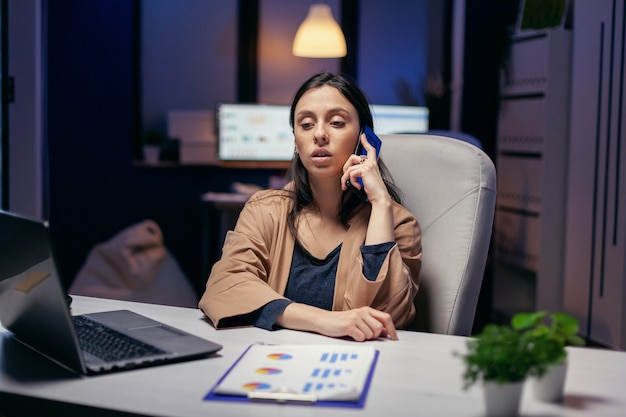 Gerente viciado em trabalho falando com o cliente ao telefone à noite. empreendedor de mulher trabalhando tarde da noite em negócios corporativos, fazendo horas extras no decorrer de um telefonema.