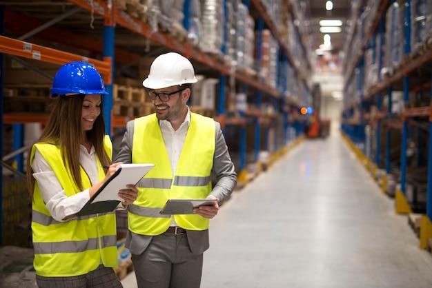 Gerentes de armazém compartilhando ideias e consultando uns aos outros sobre organização e distribuição de mercadorias