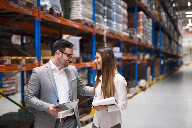 Gerentes de armazém visitando grande armazém verificando distribuição