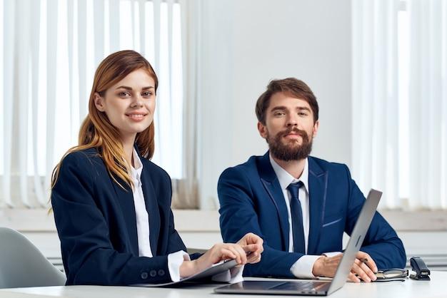 Gerentes homens e mulheres conversando à mesa em frente ao laptop de tecnologia de escritório
