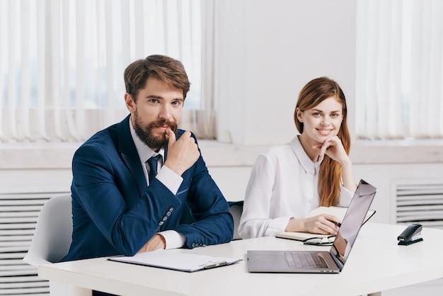 Gerentes homens e mulheres sentados à mesa em frente à equipe de tecnologia do laptop