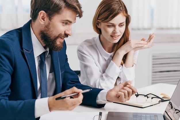 Gerentes homens e mulheres sentados à mesa em frente à tecnologia de profissionais de laptop