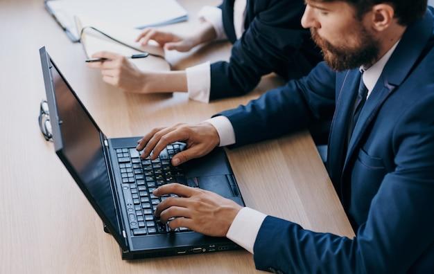 Gerentes no escritório em frente a tecnologias de rede de carreira de laptop