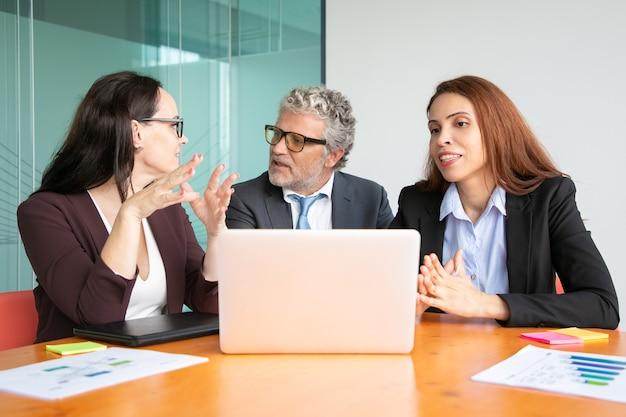 Gerentes reunidos à mesa com o laptop aberto, discutindo e compartilhando ideias com o chefe.