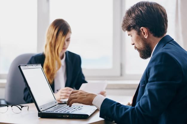 Gerentes sentados em frente a um laptop, trabalho em equipe, tecnologias de internet