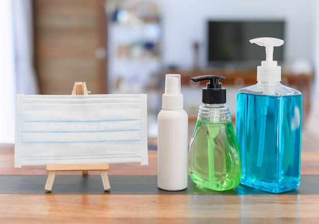 Germe de coronavírus protetor com máscaras e álcool gel ou spray de desinfetante para as mãos para lavar as mãos para proteger o vírus corona na mesa de madeira